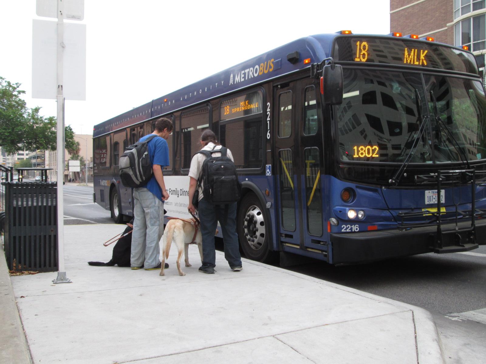 Dos personas ciegas junto a sus perros de asistencia se bajan de un bus / Fuente: Integrados Chile.