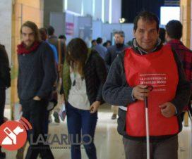 Hombre ciego caminando por una calle con peto distintivo de la Campaña Lazarillo