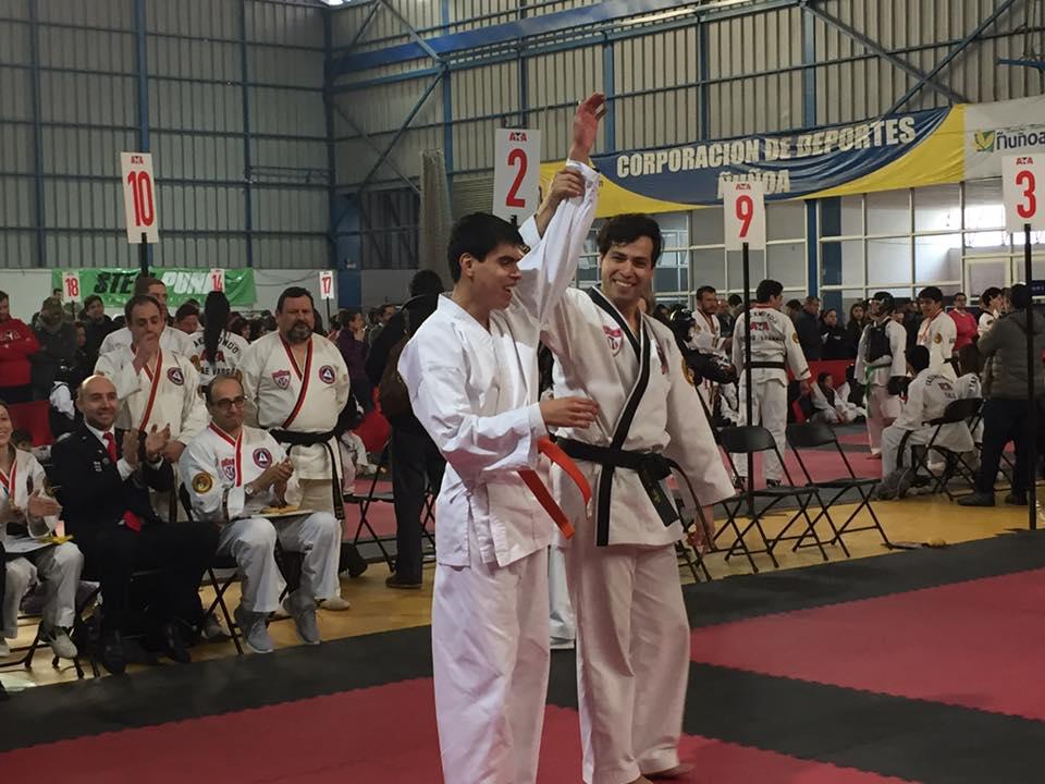 Estudiante en competencia de taekwondo junto a su guía