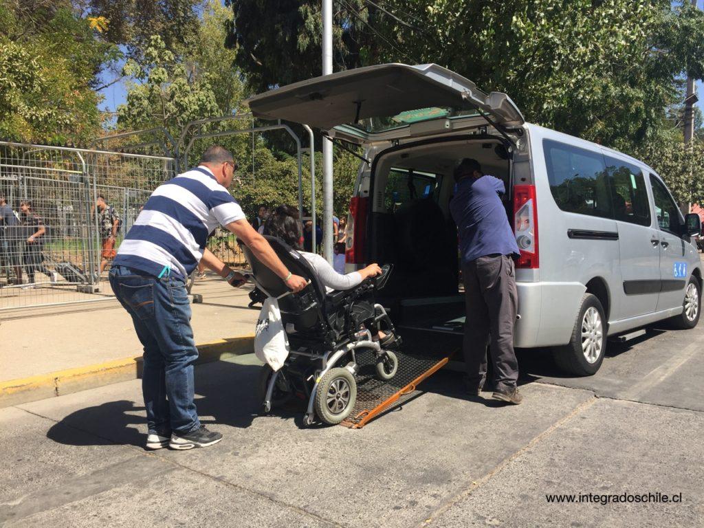 Usuaria de silla de ruedas eléctrica bajando de un van de transporte accesible provisto por la producción entre el estacionamiento y la entrada - Fuente: www.integradoschile.cl
