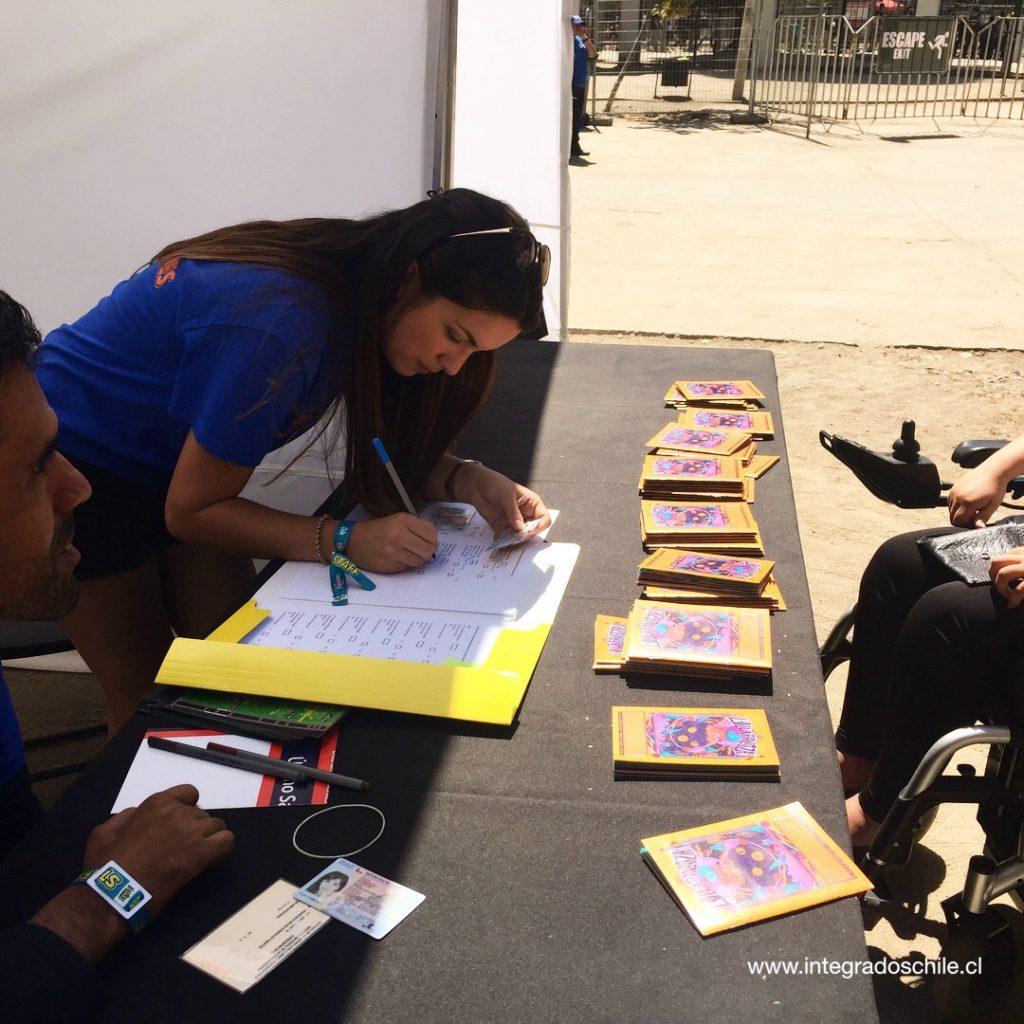 Stand de acreditación del festival inclusivo. Voluntaria llena datos de personas con discapacidad - Fuente: www.integradoschile.cl