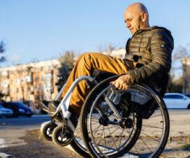 Ion Buga Dmitry Kuzuk, activista de los derechos de las personas con discapacidad en una calle transitando en su silla de ruedas. Créditos: UNDP Moldova.