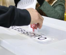 Mano de una persona ingresando un voto a una urna.