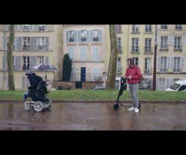 Escena de corto Électrique. Dos personas en una calle, a la izquierda una persona usuaria de silla de ruedas y a la derecha una persona de pie junto a un scooter.