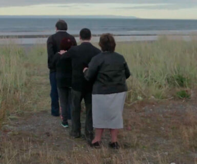 Captura de pantalla de una escena del cortometraje Los Bastones del Actor. Tres personas de espaldas, caminan en fila tomados por los hombros por un campo.