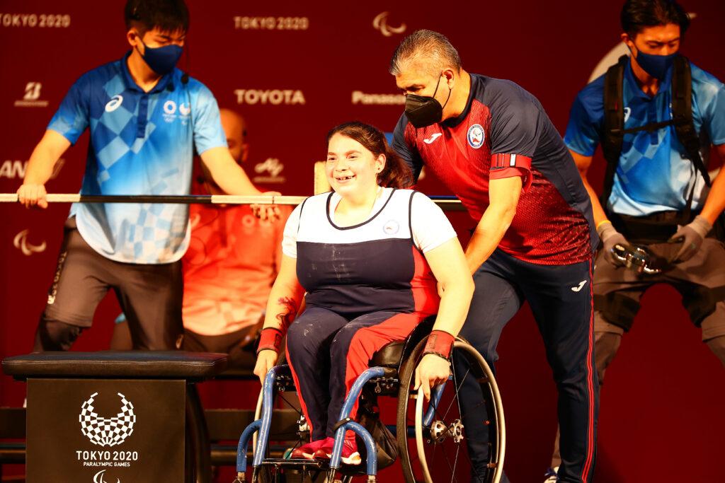 Camila Campos en su silla de ruedas, sonríe mientras es llevada por una persona de su equipo en el lugar de la competencia.