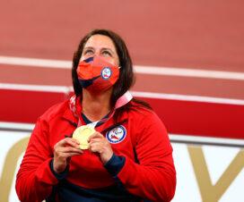Francisca Mardones sostiene con ambas manos su medalla de oro, que está colgada en su cuello, mirando hacia el cielo.